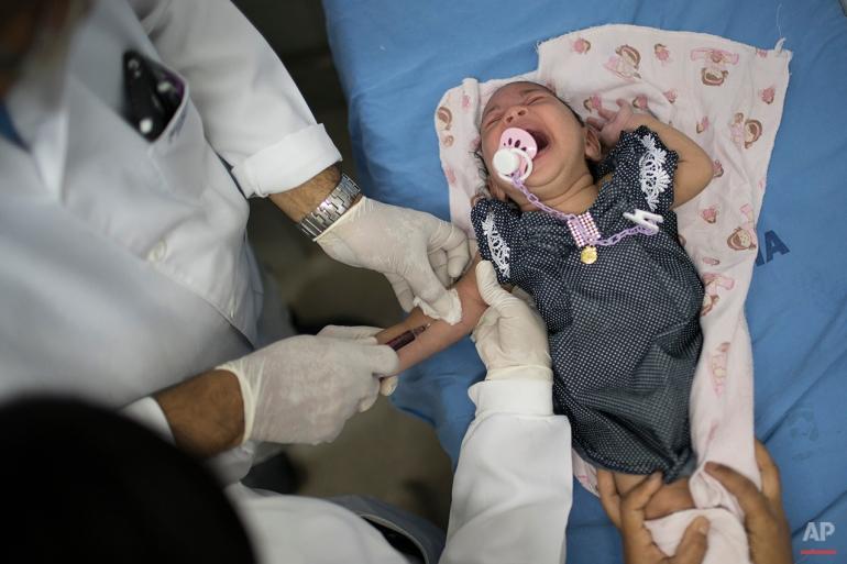 A doctor draw blood from Luana, who was born with microcephaly, at the Oswaldo Cruz Hospital in Recife, Brazil, Thursday, Jan. 28, 2016. (AP Photo/Felipe Dana)