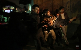 Afghan men carry a wounded man at the site of a suicide attack near a compound belonging to foreigners in Kabul, Afghanistan, Monday, Jan. 4, 2016. Afghan troops rappelled from helicopters onto the roof of a four-story building near the Indian Consulate in a northern city on Monday to drive out gunmen who had attacked the diplomatic mission the night before, officials said. (AP Photos/Massoud Hossaini)