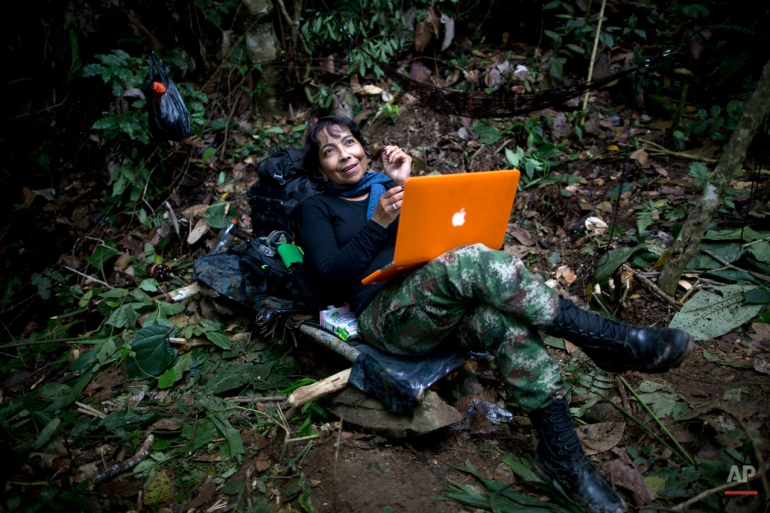 In this Jan. 4, 2016 photo, Yira Castro, a mid-level commander for the 36th Front of the Revolutionary Armed Forces of Colombia, or FARC, looks up from her laptop at a hidden camp in Antioquia state, in the northwest Andes of Colombia. After three decades in the jungle her loyalty is absolute, she says that if peace does arrive the first thing she'll do is take a trip alone with her boyfriend, a fellow rebel.  (AP Photo/Rodrigo Abd)