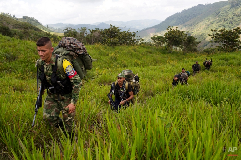 In this Jan. 6, 2016 photo, members of the 36th Front of the Revolutionary Armed Forces of Colombia, or FARC, trek to a new camp in Antioquia state, in the northwest Andes of Colombia. Big guerrilla camps are a thing of the past, the rebels now move in smaller groups. The 36th Front is comprised of 22 rank and file fighters, 4 commanders and 2 dogs. (AP Photo/Rodrigo Abd)