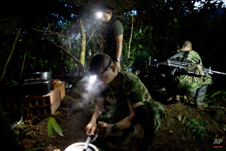 In this Jan. 3, 2016 photo, with the aid of head lamps, rebel fighters for the 36th Front of the Revolutionary Armed Forces of Colombia, or FARC, prepare a breakfast of rice, beans, sausages and coffee, in their hidden camp in Antioquia state, in the northwest Andes of Colombia. The day begins around 4:30 a.m. inside the temporary camp, home to 22 rank and file fighters, 4 commanders and 2 dogs. All rank and file are expected to share in kitchen patrol. (AP Photo/Rodrigo Abd)