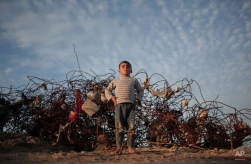 A Palestinian barefoot boy stands next to remains of a destroyed house in the town of Beit Hanoun, northern Gaza Strip, Monday, Jan. 4, 2016. (AP Photo/ Khalil Hamra)