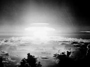 The fireball of hydrogen bomb lights the Pacific sky a few seconds after the bomb was released over Bikini Atoll on May 21, 1956 (Bikini Atoll time). Streamers at right are trails of rockets fired just before the blast for testing purposes. (AP Photo)