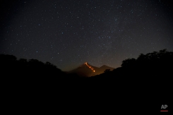 """The Volcano of Fire releases lava, seen from Escuintla, Guatemala, Monday, Jan. 4, 2016. Guatemalan authorities are on alert after the country's Volcano of Fire erupted in dramatic fashion on Sunday. Officials are asking nearby communities to remain vigilant amid a state of yellow alert. In Spanish it's known as """"El Volcan del Fuego."""" (AP Photo/Moises Castillo)"""