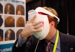 Jonathon Graff demonstrates the Apira Science iDerma light therapy device at CES Unveiled, a media preview event for CES International, Monday, Jan. 4, 2016, in Las Vegas. The device uses low-level light to treat skin conditions. (AP Photo/John Locher)