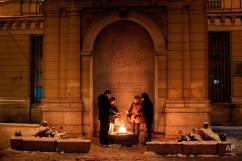 A group of tourists warm themselves up near the flame in front of monument to the fallen in World War II, in Sarajevo, Bosnia, on Monday, Jan. 4, 2016. Over the past two days, the snow has reached about 30 cm in height and has caused delays for traffic, and daytime temperatures dropped to -8 Celsius (17.6 Fahrenheit). (AP Photo/Amel Emric)