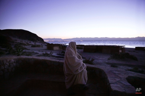 The sun rises at a camp in Newiba, South Sinai, Egypt, Monday, Jan. 4, 2016. The mountains at background show Saudi Arabia. (AP Photo/Nariman El-Mofty)