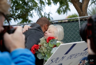 Members of the media surround unidentified staff members as they hug before returning to work at the Inland Regional Center in San Bernardino, Calif., on Monday, Jan. 4, 2016, where an attack killed 14 people on the centerís campus on Dec. 2. (AP Photo/Nick Ut)