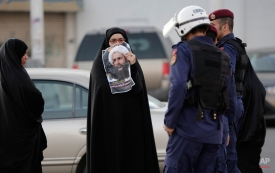A Bahraini protester holds up a picture of Saudi Shiite cleric Sheikh Nimr al-Nimr toward riot police officers in Daih, Bahrain, a largely Shiite suburb of the capital, Monday, Jan. 4, 2016. Saudi Arabia's execution of al-Nimr has sparked three days of demonstrations among Shiite Muslims. Allies of Saudi Arabia, including the monarchy in neighboring Bahrain, began scaling down their diplomatic ties to Iran in the wake of the ransacking of Saudi diplomatic missions in Iran that followed al-Nimr's execution. (AP Photo/Hasan Jamali)