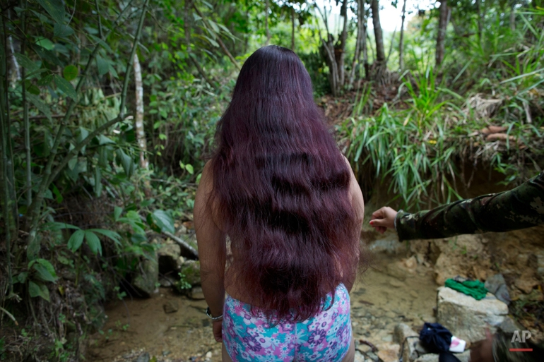 In this Jan. 5, 2016 photo, Marcela, a rebel soldier of the 36th Front of the Revolutionary Armed Forces of Colombia, or FARC, stands at the edge of a brook where she is preparing to bathe, near the guerrilla's group hidden camp in Antioquia state, in the northwest Andes of Colombia. The rebels inhabit an impenetrable forest with South America's only bear, venomous snakes and 20 species of exotic frogs. (AP Photo/Rodrigo Abd)