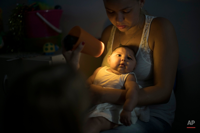 Gleyse Kelly da Silva holds her daughter Maria Giovanna, who was born with microcephaly, as she undergoes visual exams at the Altino Ventura foundation in Recife, Brazil, Thursday, Jan. 28, 2016. Brazilian officials still say they believe there's a sharp increase in cases of microcephaly and strongly suspect the Zika virus, which first appeared in the country last year, is to blame. The concern is strong enough that the U.S. Centers for Disease Control and Prevention this month warned pregnant women to reconsider visits to areas where Zika is present. (AP Photo/Felipe Dana)