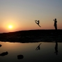 An Indian dancer taking pictures of his partner is silhouetted against the sky and reflected in the water during the last sunset of the year on the Arabian Sea coast in Mumbai, India, Thursday, Dec. 31, 2015. The two dancers who had arrived from the Indian capital for a performance in the city were spending their evening at the beach. (AP Photo/Rafiq Maqbool)