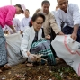 Leader of National League for Democracy party (NLD) Aung San Suu Kyi, front center, picks garbage during a clean-up drive initiated by Suu Kyi in Kawhmu, Myanmar Sunday, Dec. 13, 2015. Suu Kyi lead the garbage collection on early foggy Sunday in Kawhmu township of Yangon region, where she won her seat for the Lower House in the country's general election. (AP Photo/Gemunu Amarasinghe)