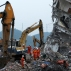 Rescuers walk past excavators near a damaged building after conducting a search for potential survivors following a landslide at an industrial park in Shenzhen, in south China's Guangdong province, Tuesday, Dec. 22, 2015. Authorities blamed an enormous, man-made mountain of soil and waste for the collapse of nearly three dozen buildings that left 81 people missing in southern China's most prominent manufacturing city. (AP Photo/Andy Wong)
