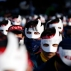 South Korean protesters attend an anti-government rally in downtown Seoul, South Korea, Saturday, Dec. 5, 2015. Wearing white half-masks and carrying flowers and banners, thousands of South Koreans marched in Seoul on Saturday against conservative President Park Geun-hye, who had compared masked protesters to terrorists after clashes with police broke out at a rally last month. (AP Photo/Lee Jin-man)