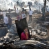 People look at the devastation caused by fire that broke out at slums in Kadivali area of Mumbai, India, Monday, Dec. 7, 2015. Hundreds of homes were reportedly destroyed as fire tenders labored to reach the source in the heavily congested area. (AP Photo/Rajanish Kakade)