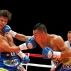Japanese champion Ryoichi Taguchi, left, gets a punch from Colombian challenger Luis De la Rosa in the first round of their WBA world light flyweight boxing title match in Tokyo, Thursday, Dec. 31, 2015. Taguchi defended his title with a technical knockout in the ninth round. (AP Photo/Toru Takahashi)