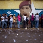 A mural of Venezuelan's late President Hugo Chavez decorates a wall outside a polling station where voters wait to enter during congressional elections in Caracas, Venezuela, Dec. 6, 2015. The system built by Chavez faces its gravest electoral test as voters cast ballots in what seems to have become a tightening race for control of the national legislature. (AP Photo/Ariana Cubillos)