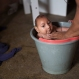 Solange Ferreira bathes her son Jose Wesley in a bucket at their house in Poco Fundo, Pernambuco state, Brazil, Dec. 23, 2015. Ferreira says her son, who was diagnosed with microcephaly, enjoys being in the water, and places him in the bucket several times a day to calm him. (AP Photo/Felipe Dana)