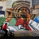 """A man cycles past a painting by Colombia's muralist Bulkar, depicting a man in traditional clothing from the coast, and playing the """"millo"""" flute, in Bogota, Colombia, Dec. 11, 2015. Artists from across Latin America, as well as Italy, were invited to paint the public areas of the Santa Fe neighborhood, as part of the city's International Festival of Revitalization through Urban Art. (AP Photo/Fernando Vergara)"""