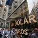 People walk outside a money exchange house in Buenos Aires, Argentina, Dec. 17, 2015. Argentina's currency sharply devalued against the U.S. dollar on Thursday as the new administration lifted deeply unpopular limits on the buying of foreign currencies. (AP Photo/Victor R. Caivano)