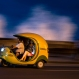 """Tourists travel in a """"Coco taxi"""" along the Malecon as waves break above the sea wall in Havana, Dec. 5, 2015. Coco taxis are one of many kinds of taxis in the capital fashioned out of motorcycles, popular with both tourists and locals. (AP Photo/Ramon Espinosa)"""