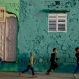 Palestinian boys run by a painted house in the Shati Refugee Camp in Gaza City on Saturday Dec. 19, 2015 photo. Shati has always been a symbol of poverty, a grey concrete jungle with 87,000 people packed into one fifth of a square mile (half a square kilometer). But now, overlooking the sewage-contaminated Mediterranean beachfront, the camp's houses are covered in vibrant colors.(AP Photo/Hatem Moussa)