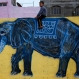 """A Palestinian boy sits atop a wall with an elephant painting in the Shati refugee camp in Gaza City, Tuesday, Dec. 15, 2015. A group of two dozen artists has painted the walls, doorsteps and facades of all the houses along a one-mile-long (1.5 kilometer-long) edge of the camp, including in the area where Hamas chief Ismail Haniya lives. Arabic at left reads: """"Osama Sabeeta."""" (AP Photo/Hatem Moussa)"""