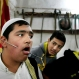 Lebanese boys look at a Muslim Sufi who pierced his cheek with metal during a religious ritual to mark Prophet Muhammad's birthday, in the southern port city of Sidon, Lebanon, Wednesday, Dec. 23, 2015. (AP Photo/Mohammed Zaatari)