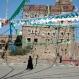A woman walks beneath decorations put up for the celebration of moulid al-nabi, the birth of Islam's Prophet Muhammad in Sanaa, Yemen, Tuesday, Dec. 22, 2015. (AP Photo/Hani Mohammed)