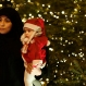 A Lebanese Shiite woman waits with her daughter to takes a picture with Santa Claus in front a Christmas tree in Downtown Beirut, Lebanon, Thursday, Dec. 24, 2015. (AP Photo/Hassan Ammar)