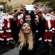 A Lebanese couple take selfie in front of men and women wearing Santa Claus costumes during a parade for Christmas, in downtown Beirut, Lebanon, Saturday, Dec. 19, 2015. (AP Photo/Hussein Malla)