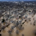 In this aerial photo, houses are surrounded by floodwater, Thursday, Dec. 31, 2015, in Arnold, Mo. Surging Midwestern rivers forced hundreds of evacuations, threatened dozens of levees and brought transportation by car, boat or train to a virtual standstill, Thursday in the St. Louis area. (AP Photo/Jeff Roberson)