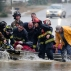 Emergency officials transport James Simmons by boat because water over Byler Road prevented them from reaching him in Moulton, Ala., Friday, Dec. 25, 2015. They carried him by boat before loading him into an ambulance. Unseasonably warm weather helped spawn severe storms Friday after violent storms in the Southeast left dozens of families homeless by Christmas Eve. (Deangelo McDaniel/The Decatur Daily via AP)