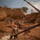 In this Nov. 13, 2015 photo, rural miners use a water pump to move rocks in a crater left behind by giant diamond mining companies, in Areinha, Minas Gerais state, Brazil. Today the devastated area known as Areinha is a no man's land where small groups of rural miners try their luck with artisan techniques, using wooden knives, metal pans, large water pumps and no infrastructure. (AP Photo/Felipe Dana)