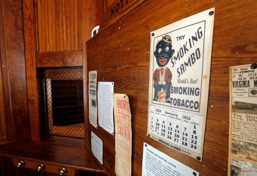 """This Wednesday, Jan. 27, 2016 photo shows a """"Smoking Sambo"""" calendar and other artifacts on display at the Montpelier Train Depot segregation exhibit in Orange, Va.. Preservationists at President James Madison's Montpelier estate, where the white-and-yellow depot is located, decided to keep the segregated waiting rooms when the structure was renovated in 2010. (AP Photo/Steve Helber)"""