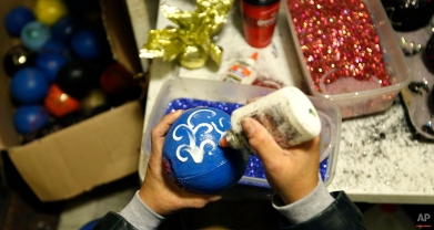 """Chanel Lafargue decorates coconuts, gorgeous pieces often referred to as """"Golden Nuggets,"""" inside her studio in New Orleans, Tuesday, Jan. 5, 2016. Lafargue has decorated tens of thousands of coconuts for her husband and his friends over the years. (AP Photo/Gerald Herbert)"""