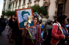 A woman carries the portrait of a civil war victim during a march on the National Day of Dignity in Guatemala City, Friday Feb. 25, 2011. Guatemalans commemorate National Day of Dignity on Friday to honor the victims of the civil war that lasted 36 years and left 200,000 people dead and 40,000 disappeared before it ended in 1996. (AP Photo/Rodrigo Abd)