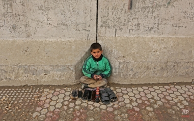 An Afghan boy working as a shoe polisher poses for a photograph, as he waits for customer in Kabul, Afghanistan, Wednesday, Feb. 10, 2016. (AP Photo/Rahmat Gul)