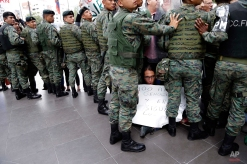 """Soldiers control a group of protesters as one sits on a sidewalk with a sign that reads in Spanish,""""100 years of Armenian genocide and Erdogan continues with the Kurds,"""" during a protest against the visit of Turkey's President Recep Tayyip Erdogan, in Quito, Ecuador, Thursday, Feb. 4, 2016. His South American three-country tour included Chile and Peru. His visits to Peru and Ecuador were the first-ever by a Turkish president. (AP Photo/Dolores Ochoa)"""