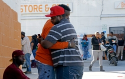 Two men embrace near the scene of a fatal shooting in Raleigh, N.C., Monday, Feb. 29, 2016. Authorities say that a police officer shot and killed a man while trying to make an arrest for a felony drug charge. (AP Photo/Gerry Broome)