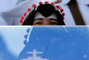 A nun smiles behind a poster welcoming Pope Francis to Venustiano Carranza stadium before Mass in Morelia, Mexico, Tuesday, Feb. 16, 2016. Francis arrived in the heart of Mexico's drug-trafficking country to offer words of encouragement to clergy trying to minister to a people tormented by the violence and gang warfare of the drug trade. (AP Photo/Gregorio Borgia)