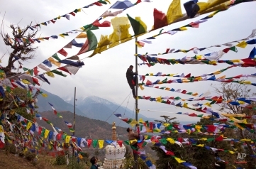 An exiled Tibetan climbs a tall post to tie multicolor prayer flags called wind horse or 'lungta' on the third day of the Tibetan New Year, in Dharmsala, India, Thursday, Feb. 11, 2016. Tibetans believe that the Buddhist prayers printed on these flags whose colors represent the five elements, earth, fire, sky, water and air, are spread on wind. (AP Photo/Ashwini Bhatia)