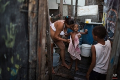 Daniele da Silva, who is seven months pregnant, dries her son Gabriel outside their home in a slum of Recife, Brazil, Friday, Feb. 5, 2016. Daniele said she had Chikungunya a couple of months ago and her ultrasound scan and other exams of her baby are normal. The Aedes aegypti mosquito is known to transmit dengue, Chikungunya and Zika, and public health experts agree that the poor are more vulnerable because they often lack amenities that help diminish the risk. (AP Photo/Felipe Dana)