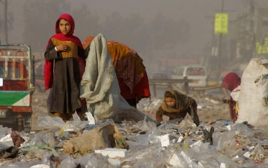 Afghan refugees girls collect recycle-able goods from a garbage to sell and earn living for their families in Peshawar, Pakistan, Friday, Feb. 5, 2016. (AP Photo/Mohammad Sajjad)