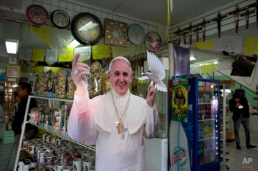 A cutout of Pope Francis holding a dove decorates a shop selling religiously-themed souvenirs and jewelry, near the Basilica of Guadalupe in Mexico City, Thursday, Feb. 11, 2016. Pope Francis, who arrives in Mexico Friday for a week-long visit, will make a stop at the Basilica, home of Mexico's beloved Virgin of Guadalupe.(AP Photo/Rebecca Blackwell)