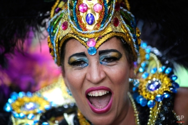 """A patient from the Nise de Silveira mental health institute dances in costume during the institute's carnival parade, called in Portuguese: """"Loucura Suburbana,"""" or Suburban Madness, in the streets of Rio de Janeiro, Brazil, Thursday, Feb. 4, 2016. Patients, their relatives and workers from the institute held their parade one day before the official start of Carnival. (AP Photo/Silvia Izquierdo)"""