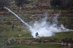 A Palestinian demonstrator throws back a tear gas canister that was fired by Israeli troops during demonstration a calling for the release of Palestinian journalist Mohammed al-Qeq, outside Ofer military prison near the West Bank city of Ramallah, Thursday, Feb. 11, 2016. Al-Qeq has refused food for over 70 days to protest his six-month imprisonment without trial or charges, an Israeli practice known as administrative detention.(AP Photo/Majdi Mohammed)