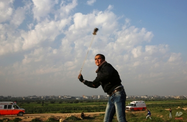 A Palestinian protester hurls stones at Israeli soldiers during clashes on the Israeli border in Gaza City, Friday, Feb. 5, 2016. (AP Photo/Adel Hana)