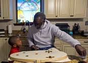 Chief of the Mohawk Hunters Mardi Gras Tribe Tyrone Casby talks to his grandson Aiden, 4, as he sews beads onto the costume he will be wearing for Mardi Gras at his home in New Orleans, Monday, Jan. 18, 2016. The Mohawk Hunters Mardi Gras Tribe is an African American group that celebrates Mardi Gras by dancing and performing in a newly created hand-made costume each year. (AP Photo/Max Becherer)